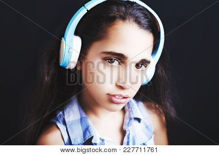 Afro-american Little Girl With Headphones Listening To Music On Black Background.