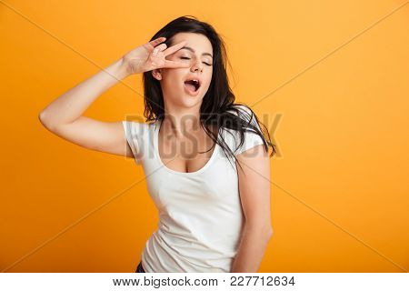 Photo of amazing pretty young woman standing isolated over yellow background wall showing peace gesture.