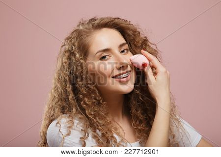 Beautiful Girl With Beauty Blender Sponge For Make-up, Curly Hair, On Pink Background. Concept Of Ap