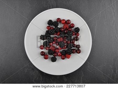 Colorful And Crisp Image Of Berries With Plate On Shale