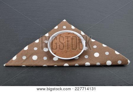 Colorful And Crisp Image Of Bowl With Cocoa Powder On Napkin And Shale