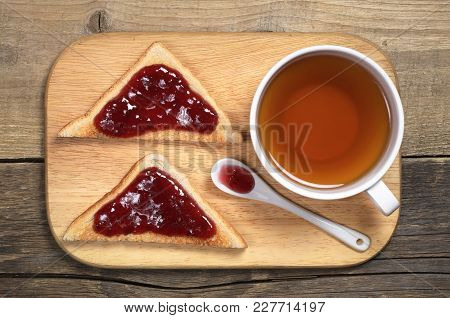Cup Of Tea And Toasted Bread With Strawberry Jam On Cutting Board On The Old Wooden Table, Top View
