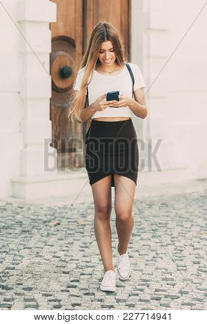 Cheerful Stylish City Girl Using Mobile App On Phone While Walking On Street. Happy Addicted Student