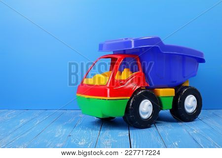 Toy Truck Dump Truck On A Blue Wooden Background.