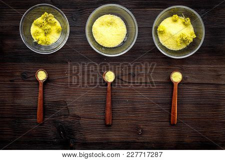 Aromatic Spa Salt. Yellow Spa Salt With Delicate Spring Flowers On Dark Wooden Background Top View.