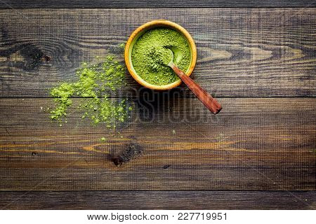 Japanese Traditional Product. Matcha Green Tea In Bowl And Scattered On Dark Wooden Background Top V