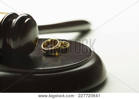 Divorce Concept. Close Up Of Wedding Rings And Judge Gavel.