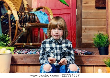 Happy little boy sitting on the porch near the wooden house. Easter holiday. Rural style, easter decoration.