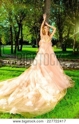Charming bride girl in a beautiful wedding dress  with lush skirt posing in a summer park.