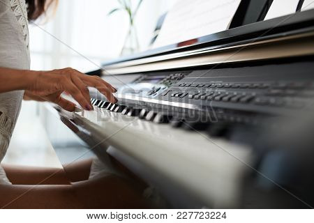 Cropped Image Of Woman Playing On Piano, Selective Focus, Buttons Are Digitally Modified
