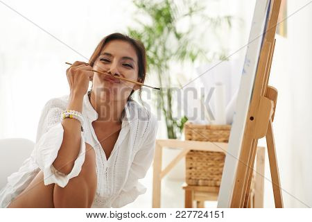 Cheerful Young Woman Making Funny Face With A Brush
