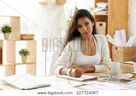 Portrait Of Beautiful Mixed-race Woman Drawing At Her Table