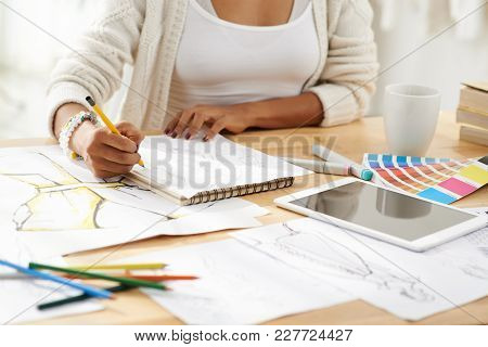 Cropped Image Of Designer Drawing Fashion Sketches In Album