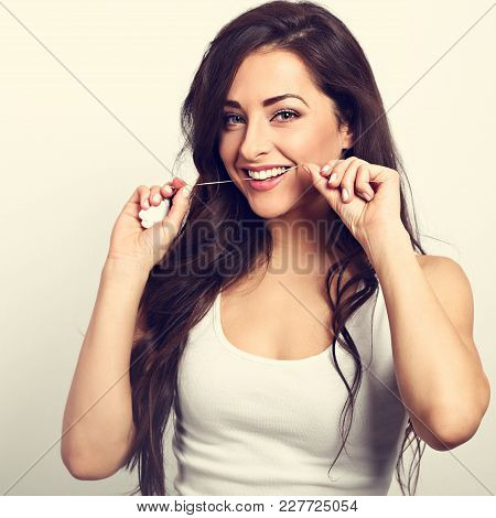 Happy Smiling Woman Cleaning The Teeth The Dental Floss. Dental Hygiene. Toned Vintage Portrait