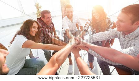 group of employees with hands clasped together.