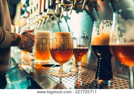 We Meet Oktoberfest. Hand Of Bartender Pouring A Large Lager Beer In Tap. Pouring Beer For Client. S