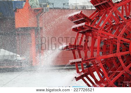 Red Paddle Wheel From A Boat On The River
