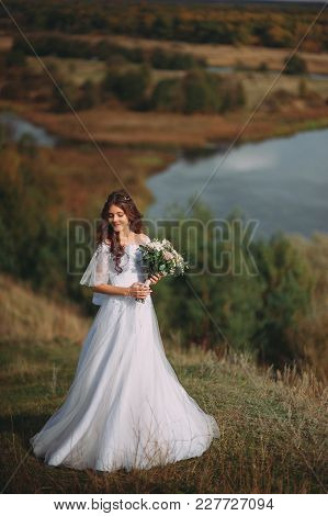 Beautiful Bride With Stylish Bouquet On The Background Of The Lake