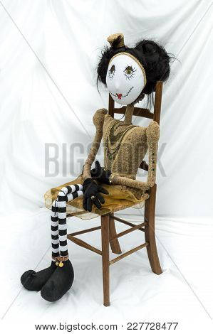 Creepy Steampunk Rag Doll Sitting On Wooden Chair. Looking Left. Lifesize Doll On A Grungy White Bac