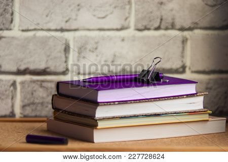 The Purple Handle Rests On A Purple Diary, A Stack Of Planings, A Black Clip, A Brick Background