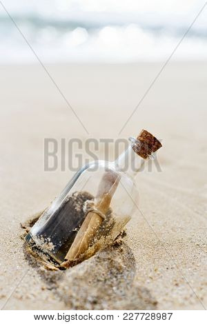 closeup of a glass bottle with a rolled message inside stranded in the sand of a lonely beach, with some blank space on top