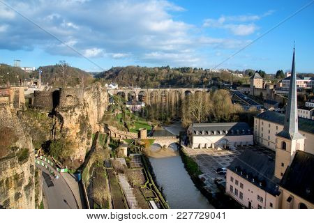 the Alzette River in Luxembourg City, Luxembourg, highlighting the Neumunster Abbey and the Saint-Jean-du-Grund Church on the right and the remains of the fortress in the Bock promontory on the left