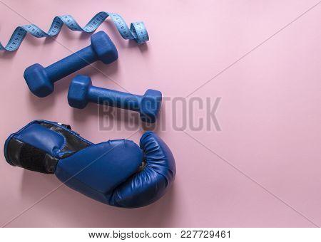 On A Pink Background Dumbbells Blue And Flying Centimeter Figure Sport Boxing Glove Soft Light
