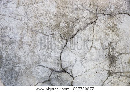 Concrete wall with cracks. Gray urban background. Space for text