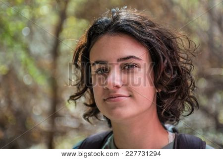 Young Teen Female With Pretty Smooth Skin And Dark Brown Hair Outdoor Portrait.