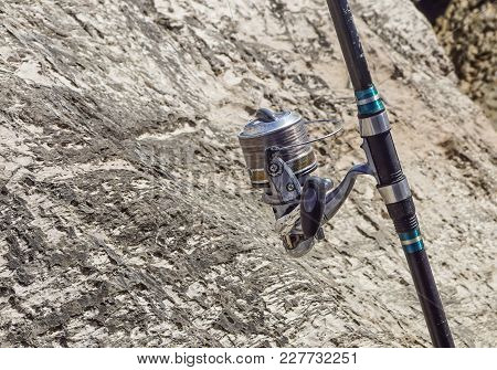 Fishing Rod With Reel Between The Rocks Ready To Be Used .