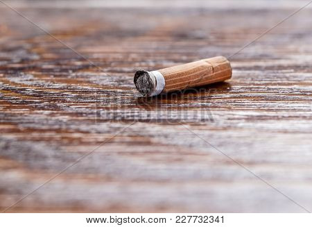Used Cigarette On The Wooden Table. Selective And Close Focus .