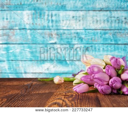 Bouquet of colored tulips placed on vintage wooden planks. Spring and Easter background with copy space