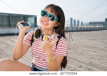 Happy Teenage Girl In Sunglasses Listening To Music On Her Smartphone And Showing Thumbs-up