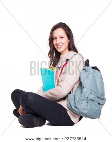 Smiling student girl sitting on the floor with legs crossed with notebooks and backpack, isolated on a white background