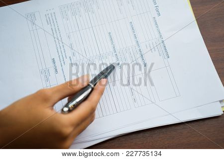 Close-up Of Hand Of Woman Holding Fountain Pen And Reading Application Form Questions. Agreement And
