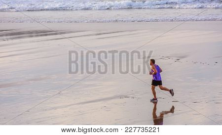 Henday, France - Sept 26, 2016:side View Of A Mature Man Doing His Jogging Alone On The Beach At The
