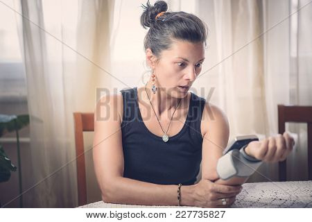 Young Woman Measuring Blood Pressure At Home, Shocked With The Measurement