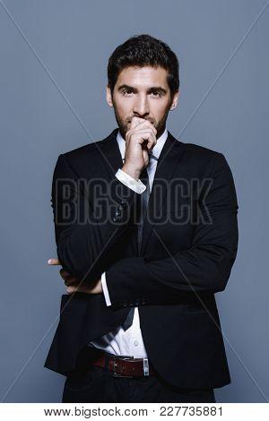 Portrait of a serious contemporary businessman in a suit. Studio shot.
