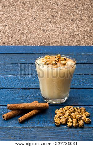 Traditional Turkish drink called Boza with cinnamon sticks and chick-pea on table.