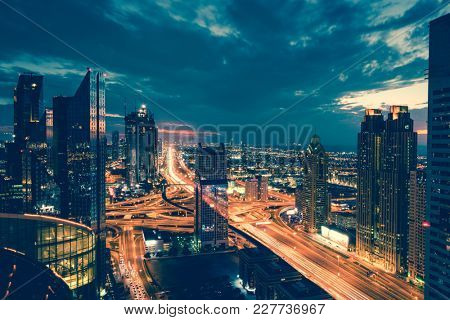 Bird's eye view of Dubai skyline and rush hour traffic in downtown at night