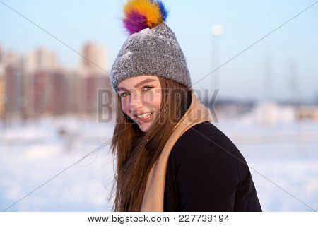 Sunny Winter Photo Of A Young Joyful Girl Dressed In A Winter Hat, Scarf, Coat And Mittens. Close-up