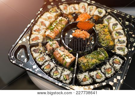 Sushi Set Nigiri And Sushi Rolls On Wooden Serving Board With Soy Sauce And Chopsticks Over Black St