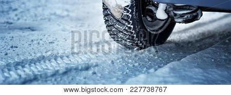 Car Tires On Winter Road Covered With Snow. Panoramic View To Vehicle On Snowy Way After Snowfall