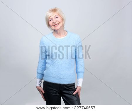 Senior Woman 70 Years Of Age On The Gray Background.