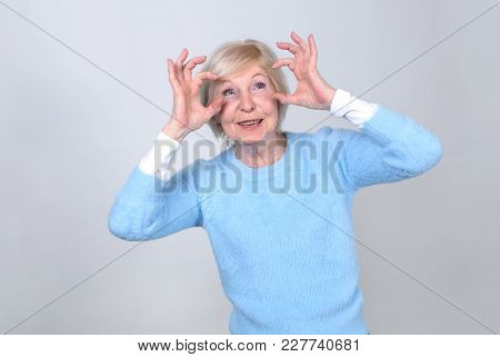 Happy Woman Shows A Gesture Of Surprise, Making The Thumbs Of The Symbol Big Eyes. Senior Woman 70 Y
