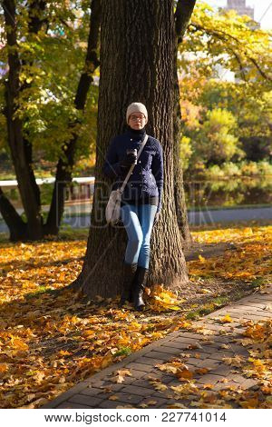 A Girl Stands Near A Tree. Autumn. Leaves Of Autumn