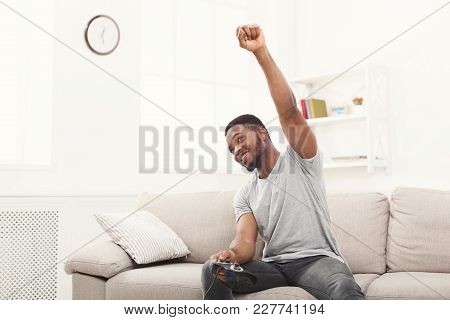 Young African-american Man Playing Video Games At Home And Winning. Happy Guy Sitting On The Couch W