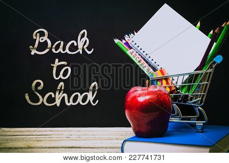 Back To School And Education Shopping Concept. Classroom With Apple, Books And Pencils On Chalkboard