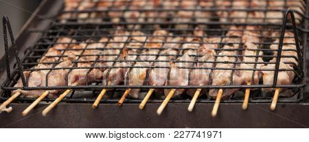 Meat skewers souvlaki on barbecue. Traditional meat on skewer cooking on charcoal. Close up, banner, front view with details.