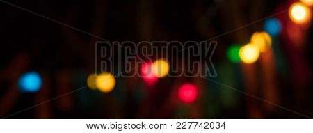Bokeh, blurred colorful circle lights on dark background. Space for text, abstract, banner.